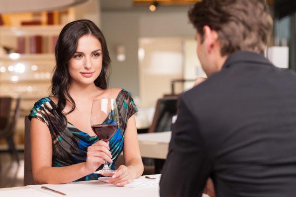 Ein Mann beim Flirten lernen und eine verführend schöne Frau, die ihren Liebhaber mit einem Weinglas betrachtet.